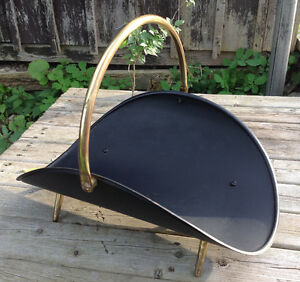 Black metal firewood stand holder with brass handle and feet