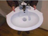 White ceramic Corner hand wash basin / sink with taps .