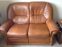 Brown leather reclining sofa and chair with matching footstool.