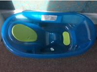 Baby bath with convenient plug moulded to support baby
