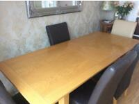 Expanding dinning table and 6 faux leather high back chairs for sale