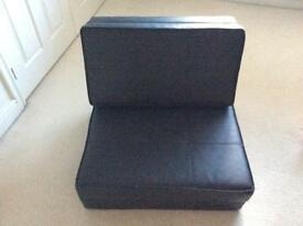 Black faux leather chair that lays flat to use as a bed