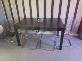 2 leaf black wood table and 4 clear plastic chairs