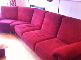 Red 5 seater Dekko Sofa. L= 4 seats(2m.) and 2 angled seats. (1.6m) D= 86cm H= 86cm Stool= 86cm2