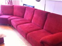 Red 5 seater Dekko Sofa. L= 4 seats(2m.) and 2 angled seats. (1.6m) D= 86cm H= 86cm Stool= 86cm2