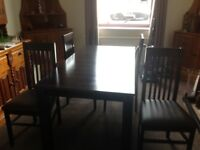 Dark wood extendable dining table and 4 chairs although will seat 6. Very good condition.