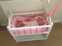 Play cot and doll that makes baby sounds