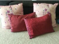 Decorative red/pink cushions and throw