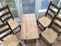 Folding winged dining table and four chairs.