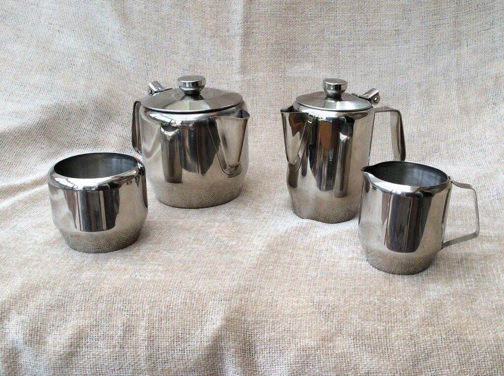 Stainless steel four piece tea set. Teapot, hotwater jug, milk jug and sugar bowl