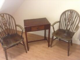 Two wheel backed carvers and an occasional table