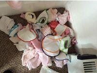 A large collection of baby girl bibs and muslins