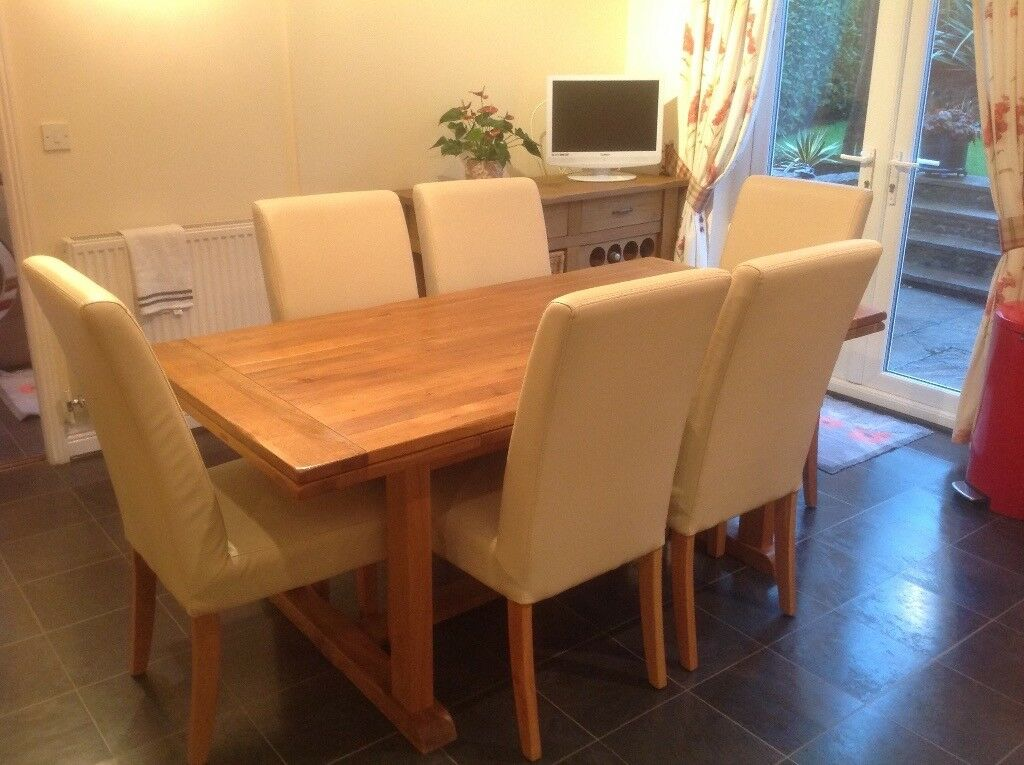 Solid wood table with six cream leather chairs plus matching side board with inter grated wine rack