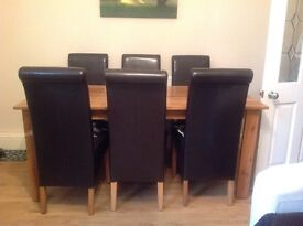 Solid oak dining table with 6 faux leather chairs