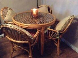 Lovely glass top table and four chairs. Cane. Cushions not included.