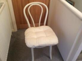 White chair with cream cushion