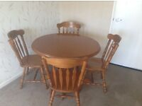 Circular wooden dining table and four colonial style chairs all items in very goodcondition
