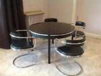 Round black wooden table and four chrome and black dining chairs