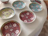 Five patterned Chinese bowls, saucers and spoons.