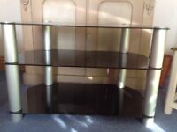 TV stand with 3 black glass shelves and silver supporting pillars