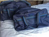 Pair of blue hold-alls by Carlton International.