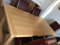 Large oak dining table plus eight bergundy leather chairs