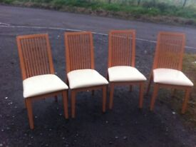 Four beech dining chairs with creme leatherette upholstery,