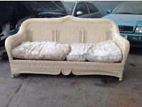 A large wicker 3 seater settee with cushions