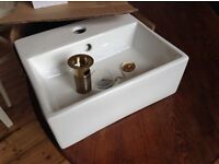 Small white ceramic sink with brass fittings