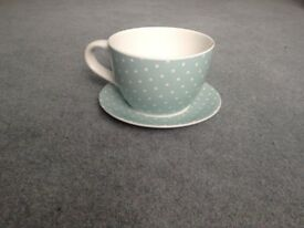 Ceramic planter in shape of giant cup and saucer. Duck egg blue with white spots.