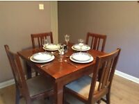 Solid oak extending dining table and four chairs