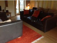 A pair of Handmade Black Leather Large Sofas