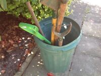 Green bin with a spade, shovel, rake and on other tool