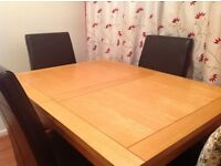 Solid oak extending dining table and four chairs.