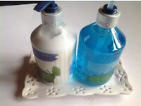 Soap and hand lotions on a pretty ceramic tray