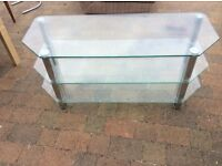 A large glass TV stand with instructions.
