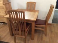 Solid oak square dining table and four chairs with leather seats