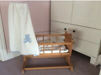 Toy wooden swinging cot with bedding.