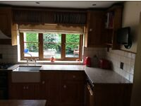 Solid wood kitchen units with integrated Smeg double oven, Neff dishwasher, granite worktop