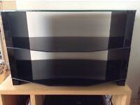 Black glass TV stand 72cm x 42cm Height 45cm. Strong and sturdy. Very good condition.