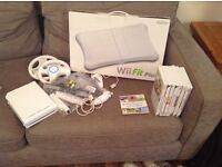 Nintendo Wii and Wii Fit board with approximately 8 games, consoles and wheels