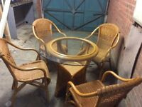 Glass topped wicker table set with 4 chairs