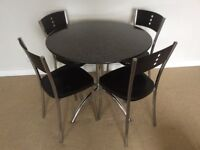 Round Granite Top Table and Black Hard Plastic Chairs
