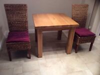 Solid oak kitchen table plus 2 high backed wicker chairs