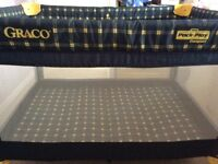 Blue and yellow Graco compact pack and play