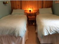 Two single divan beds, headboards and bedding.