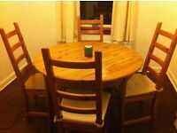 Oak round dining table with matching chairs with cushions.