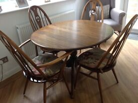Ercol extending table and 4 swan back chairs with original seat pads.
