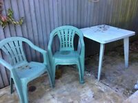 Green plastic garden table and four chairs