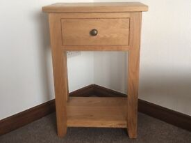 Solid oak side or telephone table with drawer and low shelf. As new.